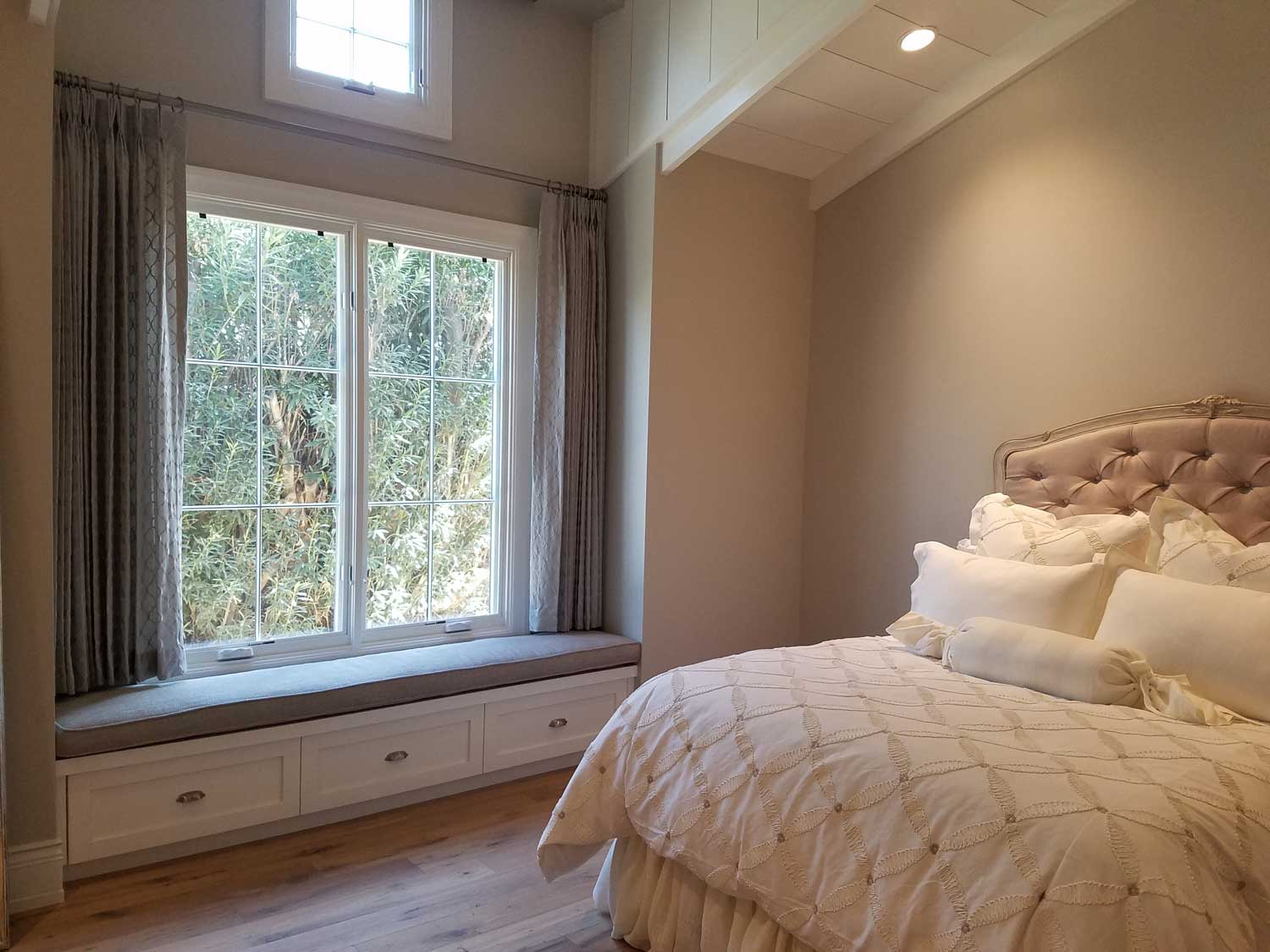 bedroom with large window with drawn drapes
